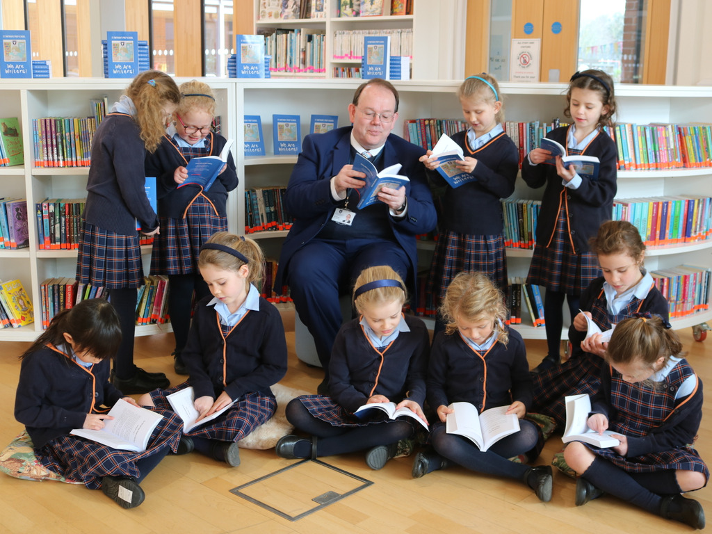 St Swithun's prep children reading their We Are Writers books with prep head Mr Brough